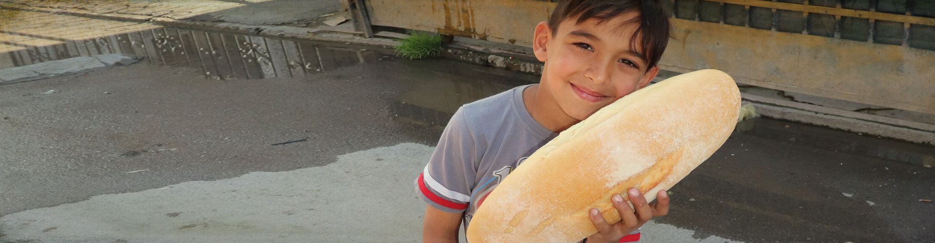 Happy boy holding a loaf of bread